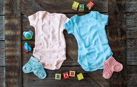 Foto de Baby clothing in pink and blue on rustic wooden background - Imagen libre de derechos