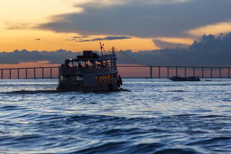 Silhouette of typical wooden boat sailing on Amazon Rio Negro near Manaus with sunset and the Manaus-Iranduba Bridge, Brazil 2015