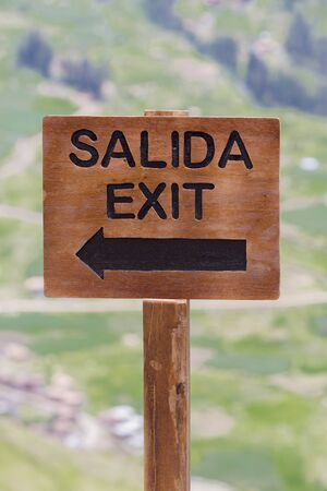 Closeup on wooden sign with Salida (Exit) written in Spanish at the Pisac Inca Ruins near Cusco. Peru 2015