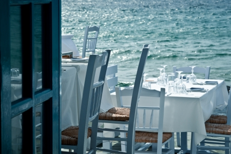 Restaurant tables on the sea in a Greek village