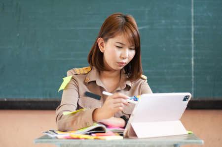 Photo pour Female Thai teacher holding notebook to the computer while smiling - image libre de droit
