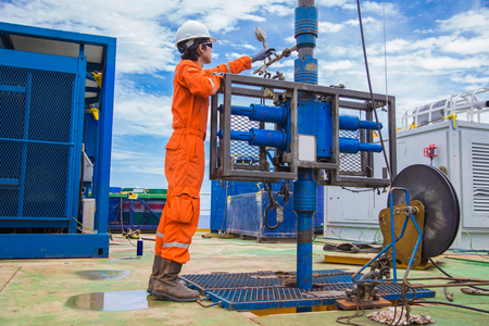 Photo pour Offshore oil and gas industry, oil rig worker inspect and setting up top side tools for safety first to perforation oil and gas production well. - image libre de droit