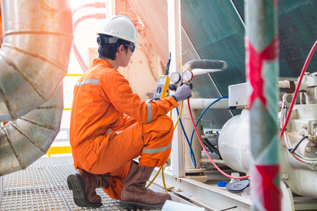 Photo pour Electrician operator inspect and checking heating ventilated and air conditioning (HVAC), air conditioning service in offshore oil rig platform while worker charging refrigerant in system. - image libre de droit