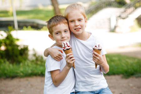 Photo for Children eat ice cream in the park. - Royalty Free Image
