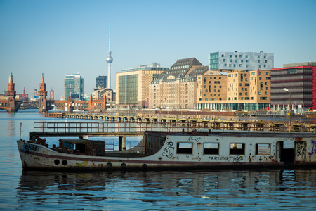 Abandoned old boat on the river Spree in Berlin with skyline in background