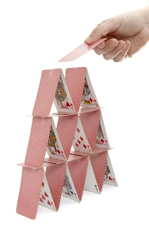 close up of house of playing cards and hand on white background with path