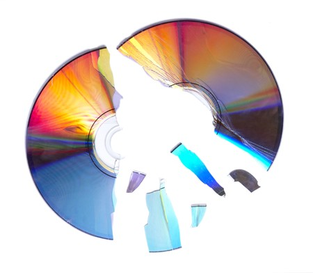 close up of broken compact disc parts on white background