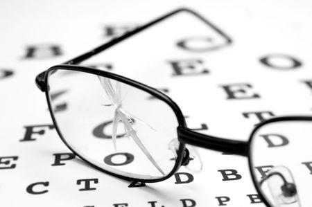 Photo pour close up of broken glasses and snellen chart - image libre de droit