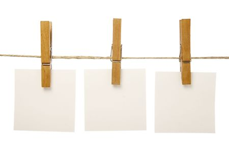 close up of postit reminders and clothespins attached to a rope on white background
