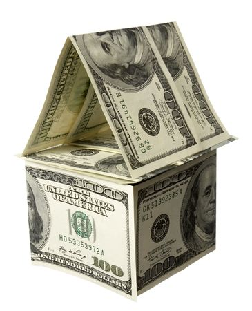 close up of miniature house  built of paper currency on white background