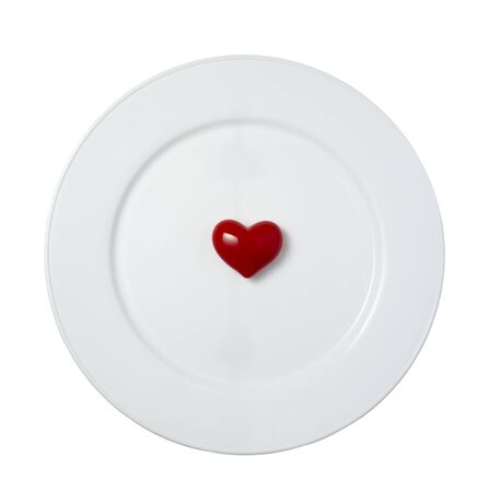 close up of red heart shape object on white plate  on white background
