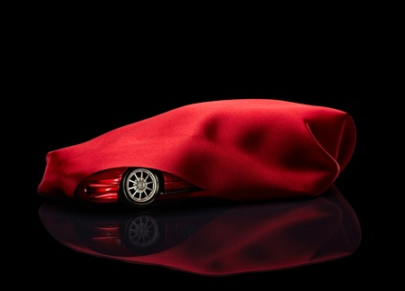 close up of  a new car hidden under red cover on black background