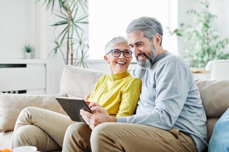 Photo pour portrait of happy smiling senior couple using tablet at home - image libre de droit