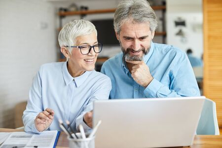 Foto de portrait of two senior  businesspeople discussing over a laptop in the office - Imagen libre de derechos