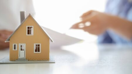 Photo pour House model with agent and customer discussing for contract to buy, get insurance or loan real estate or property background. - image libre de droit