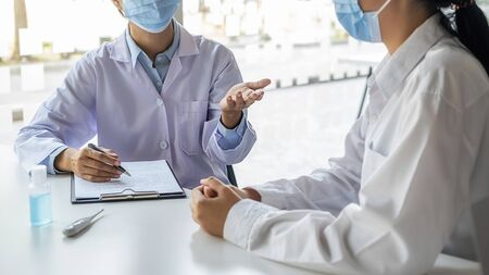 Photo pour Doctor consulting patient, working on diagnostic examination on Coronavirus disease while writing on prescription record information document in clinic or hospital office. Medical and Health concept. - image libre de droit