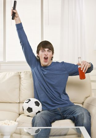 A young man is sitting on the couch in his living room and watching a sports game.  He is holding a remote control, a soda, and there is a soccer ball right next to him.  He is looking at the camera.  Vertically framed shot.