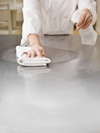 A chef is cleaning a counter in a professional kitchen with a bottle of solution and a rag.  Vertically framed shot.