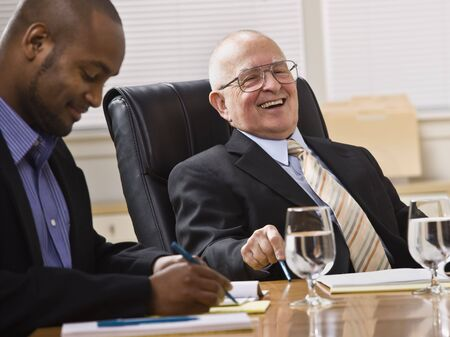 An elderly man and a young businessman are seated together at a desk in an office.  They are laughing and looking away from the camera.  Horizontally framed shot.