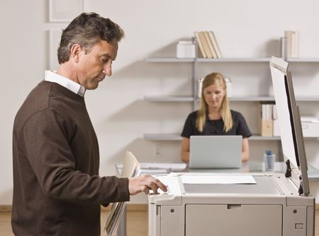 A businessman is making copies in an office.  There is a woman behind him at a desk.  He is looking away from the camera.  Horizontally framed shot.