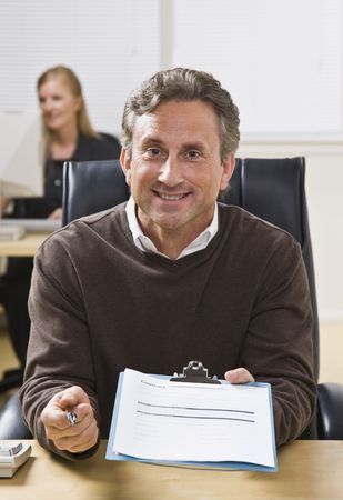 A businessman is holding a clipboard out in front of him and is smiling at the camera.  There is a woman in the background.  Vertically framed shot.