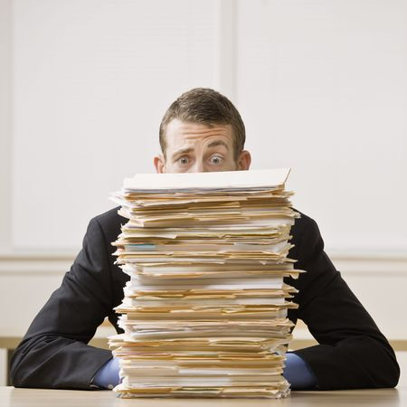 Foto de Business man behind tall stack of folders. Square format. - Imagen libre de derechos