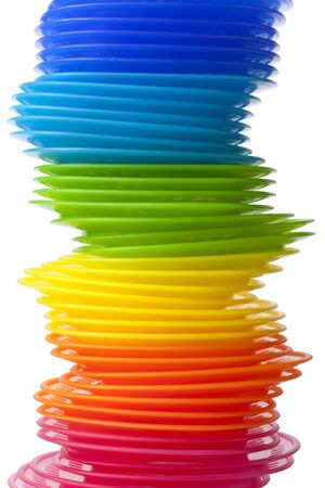 Rainbow colored plastic plates on white background