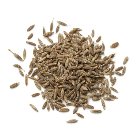 Heap of dried cumin seeds on white background