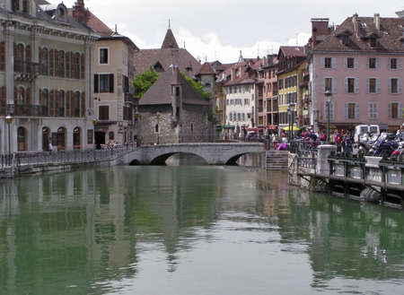 Tourists around  the 12th century  Palais de l'Isle,located close to the Thioux River,  Annecy, Haute Savoie,France. It became a jail in the 14th century. Annecy also called Venice of the Alps is a very popular tourist attraction