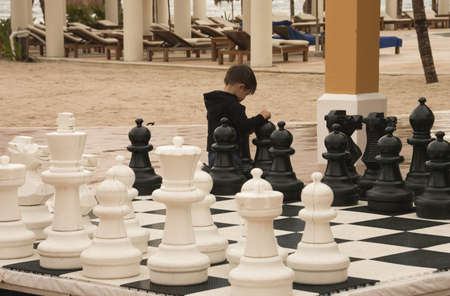TULUM, MEXICO - DECEMBER 10TH;  little boy playing chessboard during his holidays in a Caribbean destination scenic, Tulum, Mexico, 10th December 2006