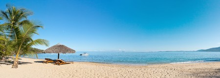 Photo pour Tropical beach panorama with deckchairs, umbrellas, boats and palm tree - image libre de droit
