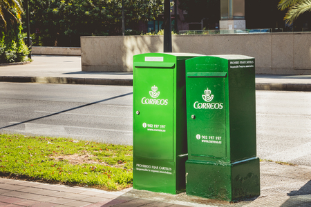 VALENCIA, SPAIN - June 18, 2017 : in the street, green mail boxes of the company Correos, the main public postal operator in Spain, wholly owned by the state of Spain