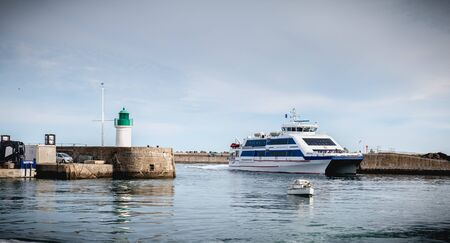 Ile d Yeu, France - September 16, 2018: ferry that enters the harbor of the island of Yeu where travelers are sitting to admire the show on a summer day