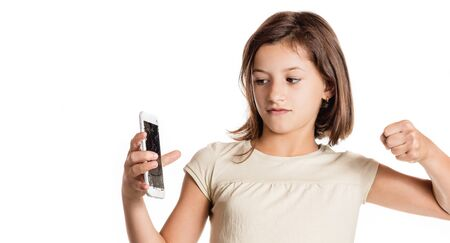 Photo pour angry little girl holding a smartphone with broken screen in studio - image libre de droit