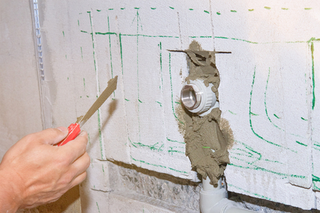 Builder holds a spatula in his hand and covered with cement mortar hole with pipe in the wall with lens flare.