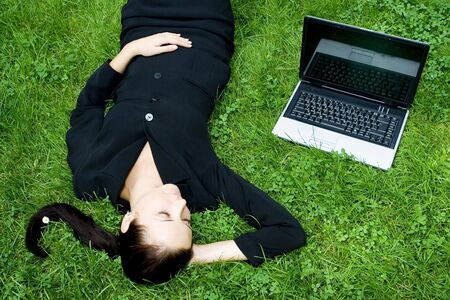 Businesswoman lying on grass with laptop