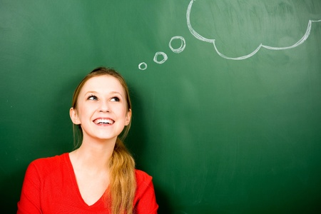 Woman standing next to thought bubble on blackboard