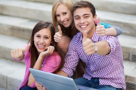 Photo pour Friends with laptop showing thumbs up - image libre de droit