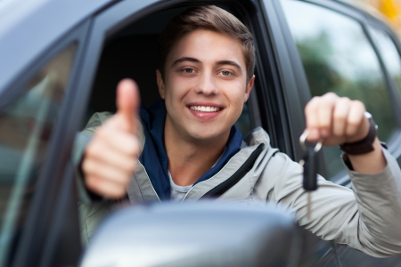 Young man doing thumps-up in car