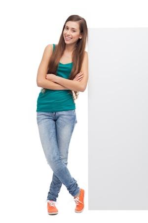 Photo pour Woman leaning against blank billboard - image libre de droit