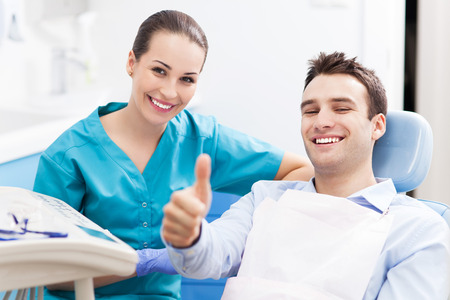 Photo pour Man giving thumbs up at dentist office - image libre de droit