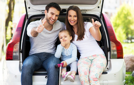 Family in car showing thumbs up