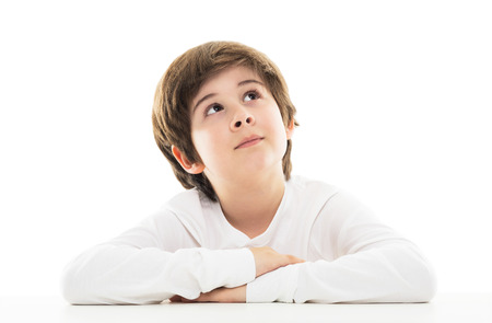 Boy sitting at table looking up