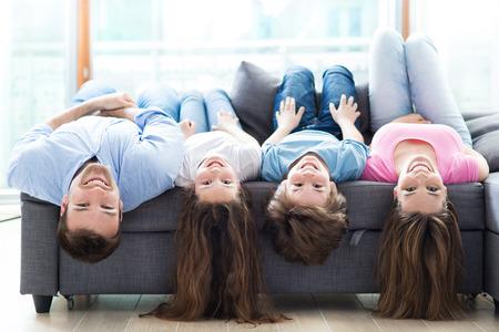 Photo pour Family lying upside down on sofa - image libre de droit