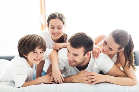 Photo pour Family of four lying on bed - image libre de droit