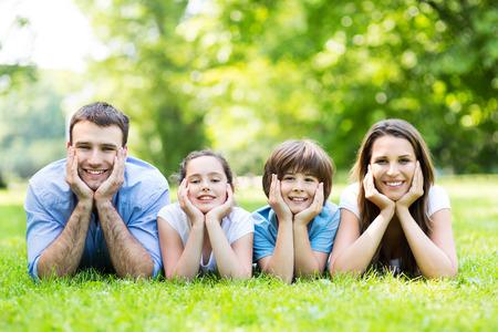 Photo pour Family outdoors lying on grass - image libre de droit