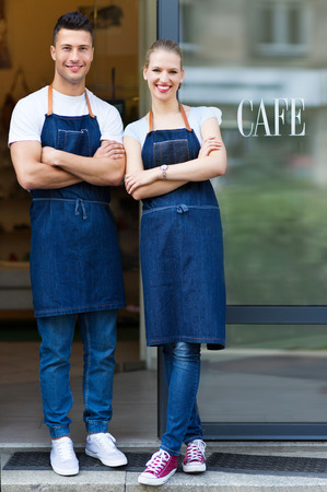 Young cafe owners in doorway