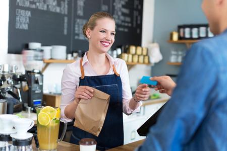Photo pour Waitress serving customer at the caf - image libre de droit