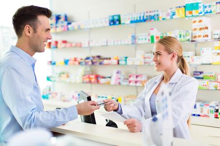 Photo pour Pharmacist and client at pharmacy - image libre de droit