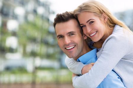 Photo pour Young couple smiling outdoors - image libre de droit